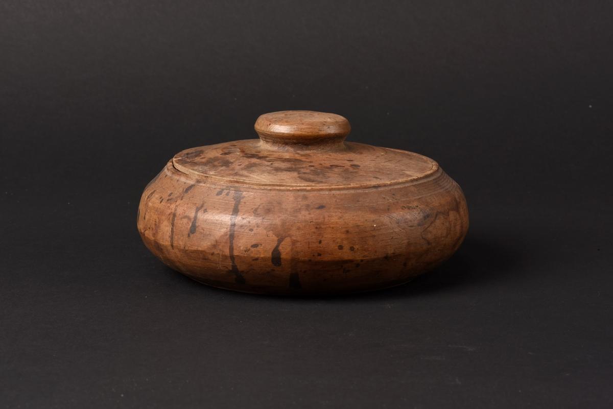 Rund svarvad smörask med lock, tillverkad av ek. Locket har ett runt knopphandtag.