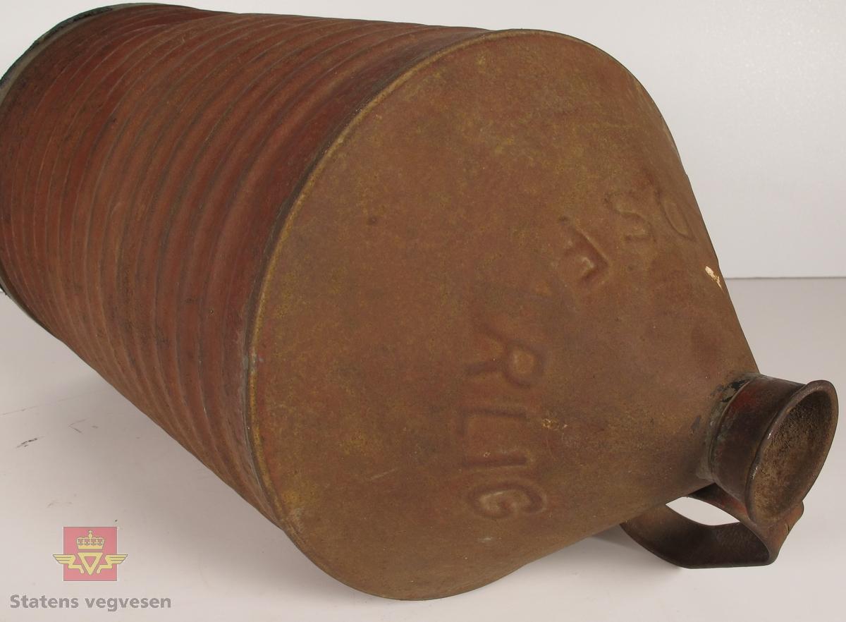 Sylinderformet kanne med bærehåndtak i metall. Kannen har horisontale riller, og smaler inn til en tut i toppen. Har skiften ILDSFARLIG innpreget i metallet. På undersiden står CAS. skrevet i svart. Har vært rødlakkert, men har bare rester av lakken. Mangler kork.