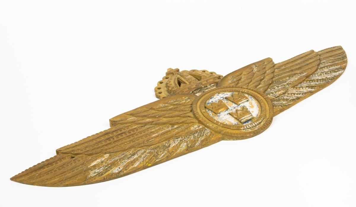 Flygvapenemblem m/26. Bemålad och förgyld relief av trä i form av en flygarvinge.