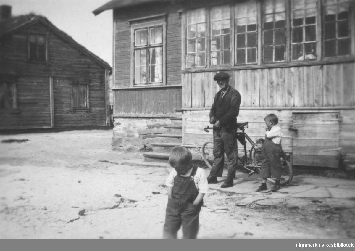 En mann og to barn foran et hus (havnefogd Nilsen sitt hus) i Salttjern. Mannen lener på en sykkel.