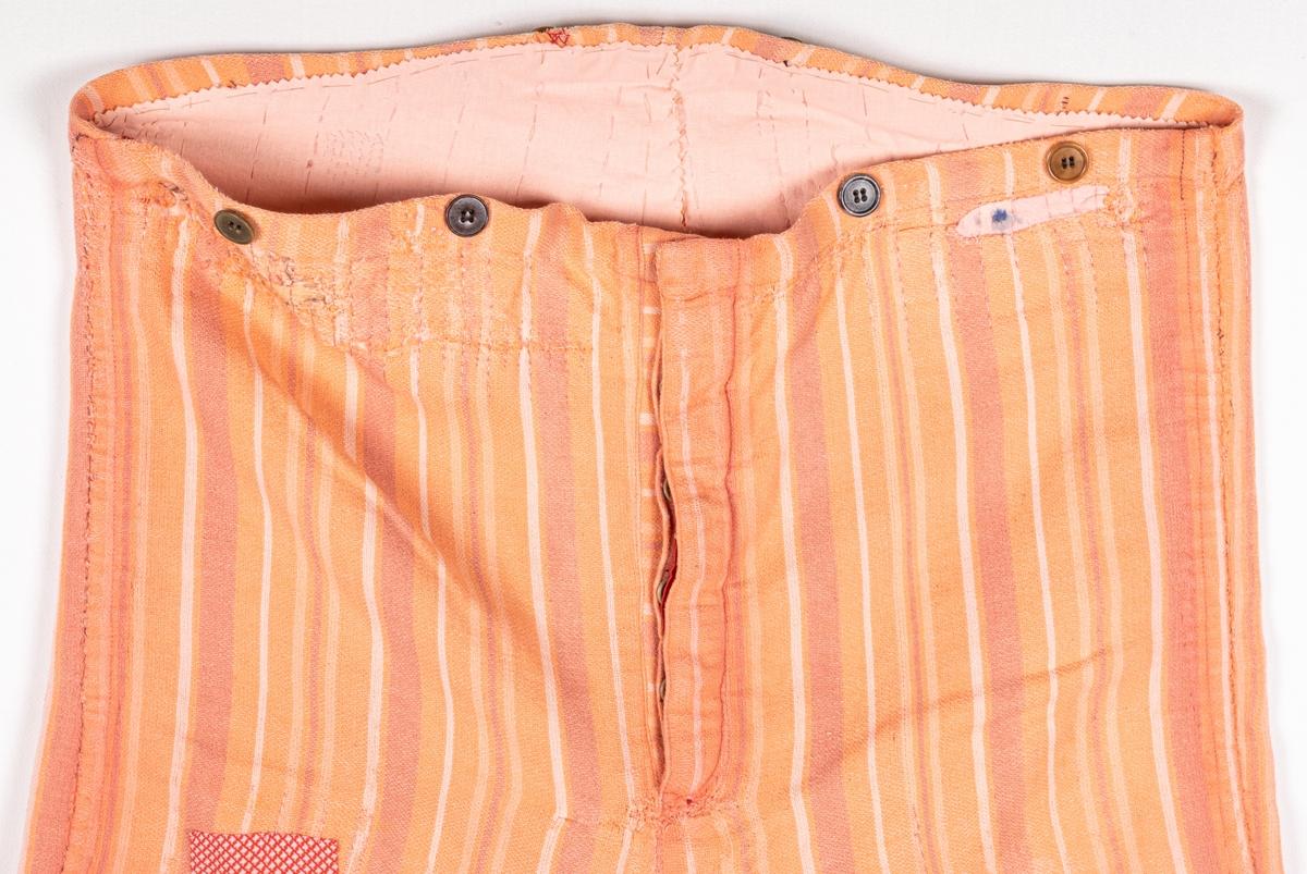 Byxor av bomullsflanell mönstrade i vertikala ränderr i olika skära toner. Slag nedtill. Gylf med knappar. Knappar för hängslen i linningen. På höger knä är en stor lapp i rödvitrutigt tyg. Revor upptill lagade med lappar på insidan. Har tillhört cirkusartisten Charles Bazola. Gåva till Länsmuseet 1987 av dotterdottern Elly Lindeborg, Gävle