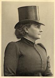 Porträttfoto av en kvinna i riddräkt med hög hatt. Midjebild