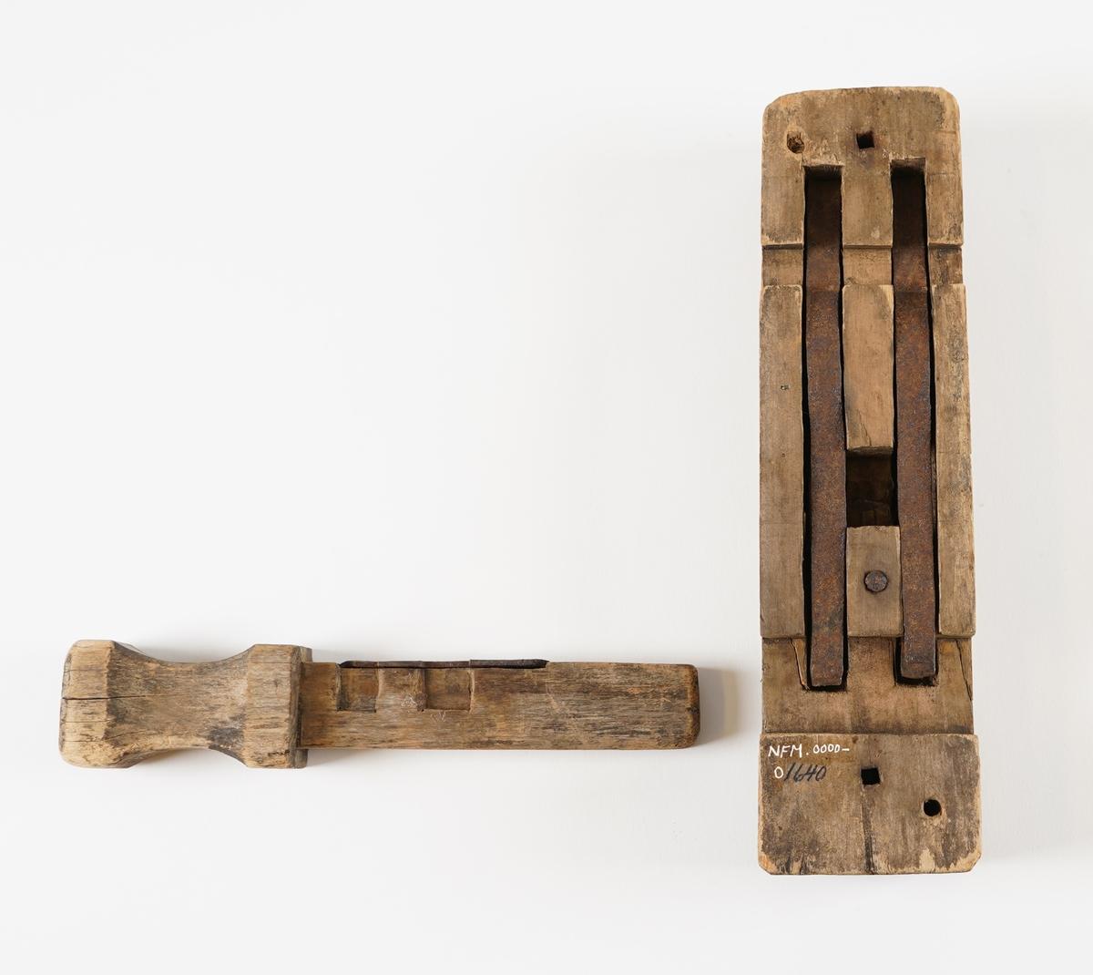 Ein trelås med stålfjører. Ein trekloss med innfelte stålfjører og eit handtak som er felt inn tvers over klossen.