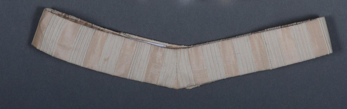 Et kjoleliv sydd av champagnefarget/ecrufarget silkelignende stoff. Det er ivevde striper i ulike nyanser av denne fargen og hvitt. Den har vide ermer med blonder på mansjettene. Dett er også en blondeinnfelling i brystet/i front. Blonden er sydd på et lyst stoff. Lukkingen (ved hjelp av hekter) er skjult i innfellingen. I halslinningen er det innfelt uforet blonde. Halsen er høy og det er hekter for åpning/lukking bak. Kjolelivet er ettersittende i livet. Det er isydd 4 spiler i livet, samt 3 spiler i halslinningen. Nede er kjolelivet kantet med skråbånd. Midt bak er det sydd på en hekte til å feste skjørtet på. Hele kjolelivet er foret med sateng i samme farge. Til kjolelivet hører det til et foret belt av samme type silkelignende stoff som kjolelivet. Beltet er fasongsydd og lukkes med hekter.