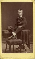 Foto av en pojke i jacka och byxor. Han sitter uppflugen på