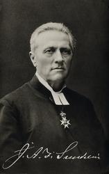 Foto av en man klädd i prästrock och prästkrage. Under präst