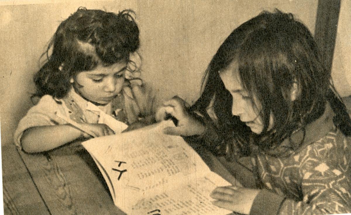 """Vid en skolbänk sitter två små flickor och tittar i en lärobok. Bilden är troligtvis tagen i samband med någon av de kurser som arrangerades för romer i mitten av 1900-talet, som kompensation för förlorad skolgång. Stiftelsen Svensk Zigenarmission, grundad 1945, drev sommarskola för romska elever under hela 1940- och 1950-talen. Eleverna var mellan 6 och 60 år och satsningen blev mycket medialt uppmärksammad. Zigenarmissionen var dock kritiserad, både av romer och icke-romer, då man ansåg att romska barn skulle få samma möjligheter att gå i skola som andra svenska barn.  Efter en tid med olika former av försöksverksamhet föreslog den s.k. """"Zigenarutredningen"""" (1954), att romer skulle gå i vanliga skolor. Frågan om undervisningens organisering fick de enskilda skolorna att hantera på egen hand men från och med juni 1960 fanns möjlighet för kommuner att rekvirera bidrag från staten för speciell undervisning av romska barn. Undervisning för romer arrangerades även av bland annat folkhögskolor och studieförbund. Först efter att alla romer fick bli bofasta på sextiotalet, fick samtliga svenska romer tillgång till skolundervisning."""