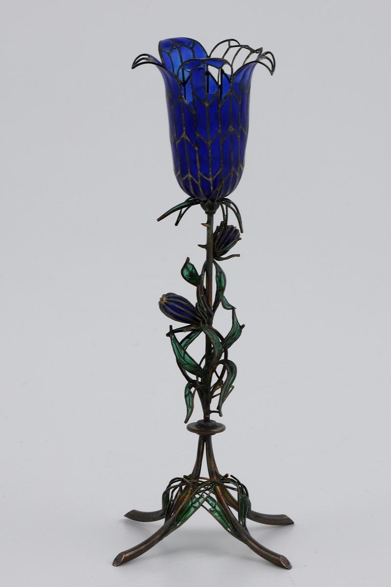 Vase i vindusemalje og forgylt sølv. Utformingen skal minne om en blåklokke, og vasen hviler på fire svungne ben. På den forgylte stengelen er det fremstilt blader samt to små blomsterknopper, utført i transparent grønn og blå vindusemalje. Vasen krones av et fembladet blomsterbeger i blått. Uten stempel.