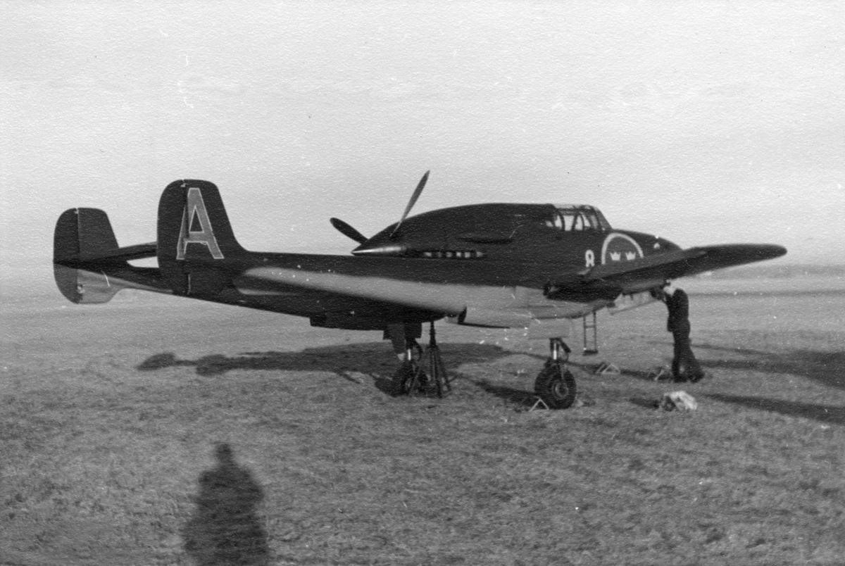 Flygplan Saab J 21A tillhörande F 8 Barkarby på ett flygfält, 1940-tal. Vid vingen står en flygmekaniker.