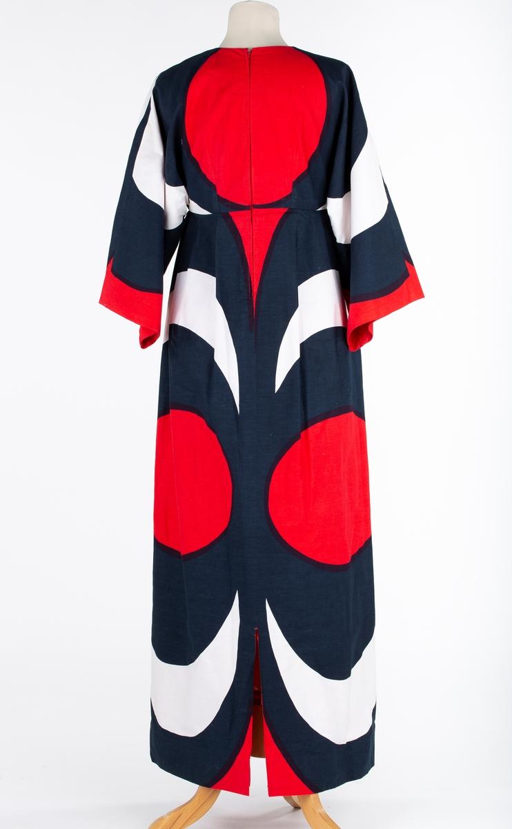 Lang kjole. stormønstret stoff antakelig fra Marimekko. Høyt liv med kimonoermer, rund halsringing, lengdesnitt forran og bak, glidelås midt bak. Rett skjørt i 3 bredder lagt i legg mot livet. Splitt midt bak. Helforet med rødt syntetisk forstoff Halvlang erm, høyt liv , legg på skjørt. Helforet. Mønster i form av store, konsentriske sirkler i sterke farger.  Kjolen sydd av Aase Weydahl-Ottesen Kjolen i fod stand . Foret noe skittent ved halsringing og armhule