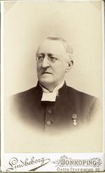 Foto av en äldre man med glasögon, klädd i prästrock och prä