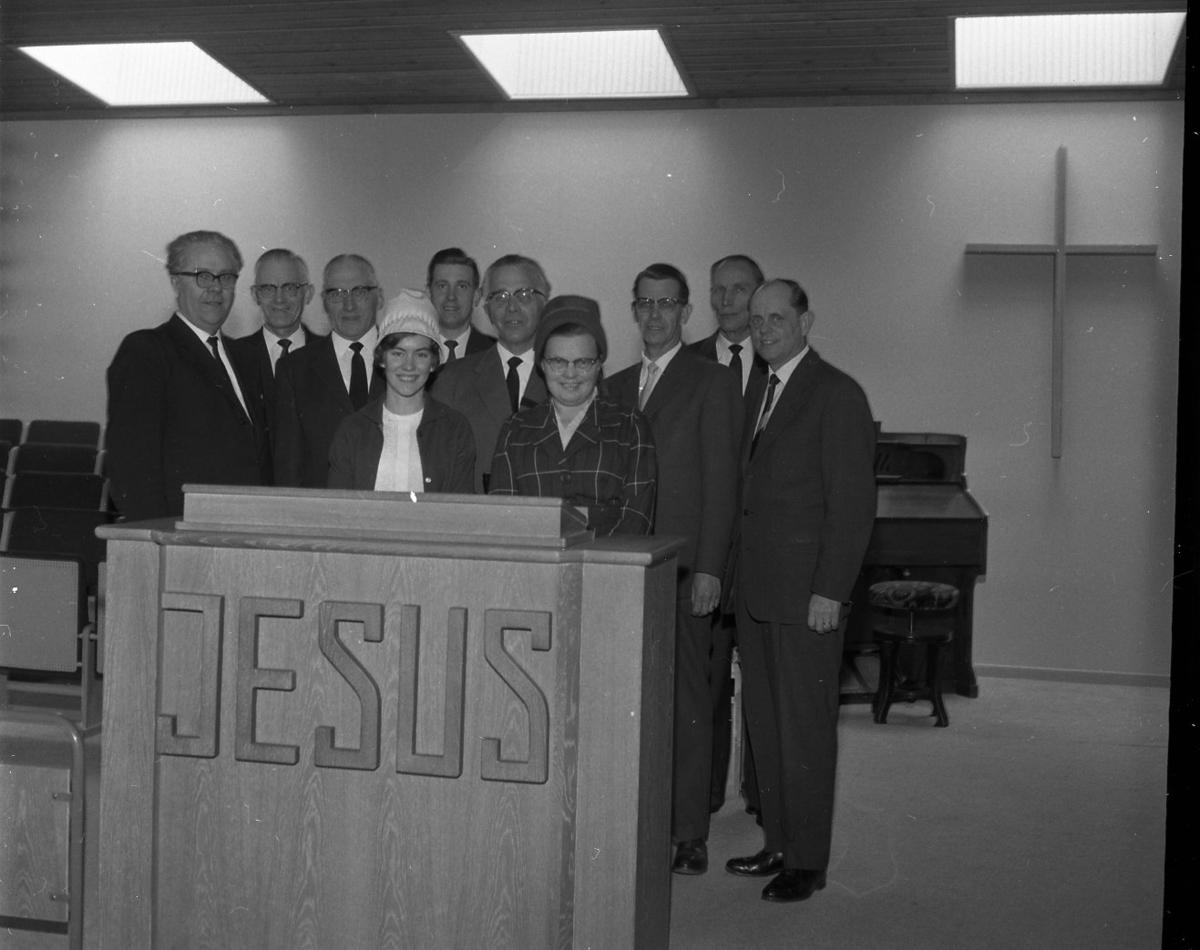 """Åtta kostymklädda män och två kvinnor med hatt står bakom talarstolen i Filadelfiakyrkan. På densamma, mot salen, står texten """"JESUS"""". Mannen som står mellan kvinnorna är pastor Robert Svensson."""