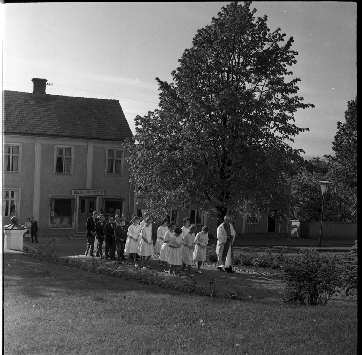"""Konfirmander på väg in till Gränna kyrka med kyrkoherde Wallis Wendel i täten. Utmed Brahegatan skymtar en fastighet med skylten """"Helge Peterson"""""""
