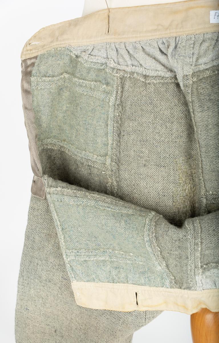 Guttebukse, ull, diagonalvevet melert stoff. Kanskje håndvevet. Hjemmesydd satt sammen av 15 smålapper fra ulike plagg. Linning i lerret m/knappehull for seler. Splitt i sidene lukkes med knapping, begge knapper mangler. belegg av forstoff på den bakre siden an ssplittene.. Gylfen er bare et åpent hull (åpning i sømmen). Avklippet bukseben ; kanten forsterket med heklet kant.  Opplysning om giver og bruker mangler