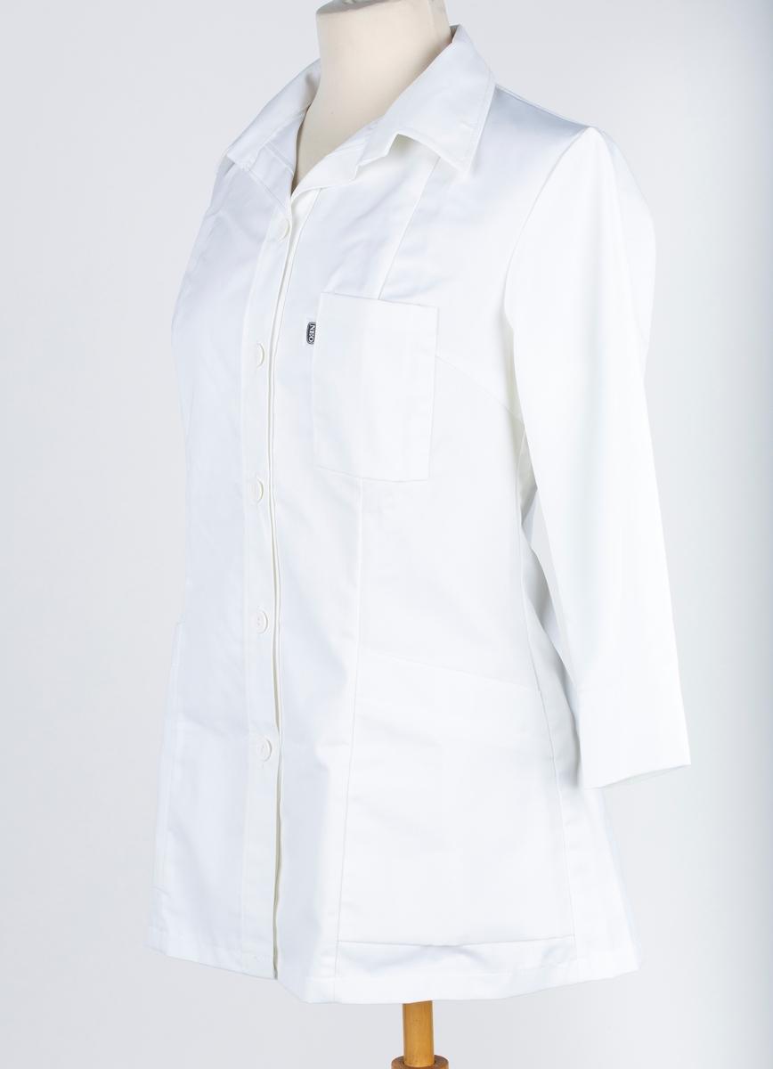 Skjorte, 7 bredder, med slag, 3 lommer, lange ermer, 3/4 lang. Neo yrkesklær. Sannsynligvis laboratoriefrakk.