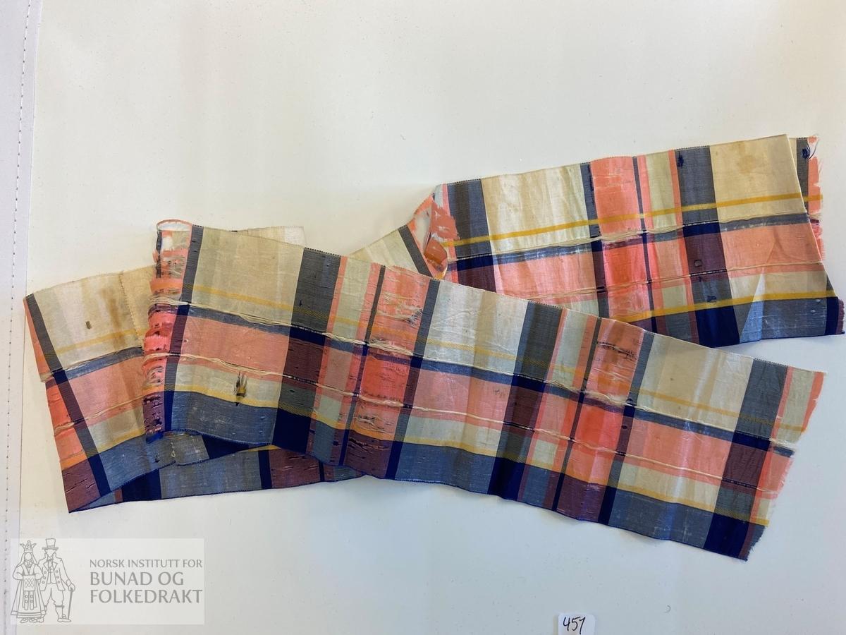 Band, silkeband. Breitt band av silketaft, lerretsbinding. Ulike fargar i renning og innslag som dannar rutemønster. Nokre stripeeffektar i renningsretning, i sateng og rips. Jare i sidene. I fargane marineblått, rosa, gult, og eggekvitt. Skøytt midt etter lengda. Dei to lengdene sydd saman med maskinstikning.