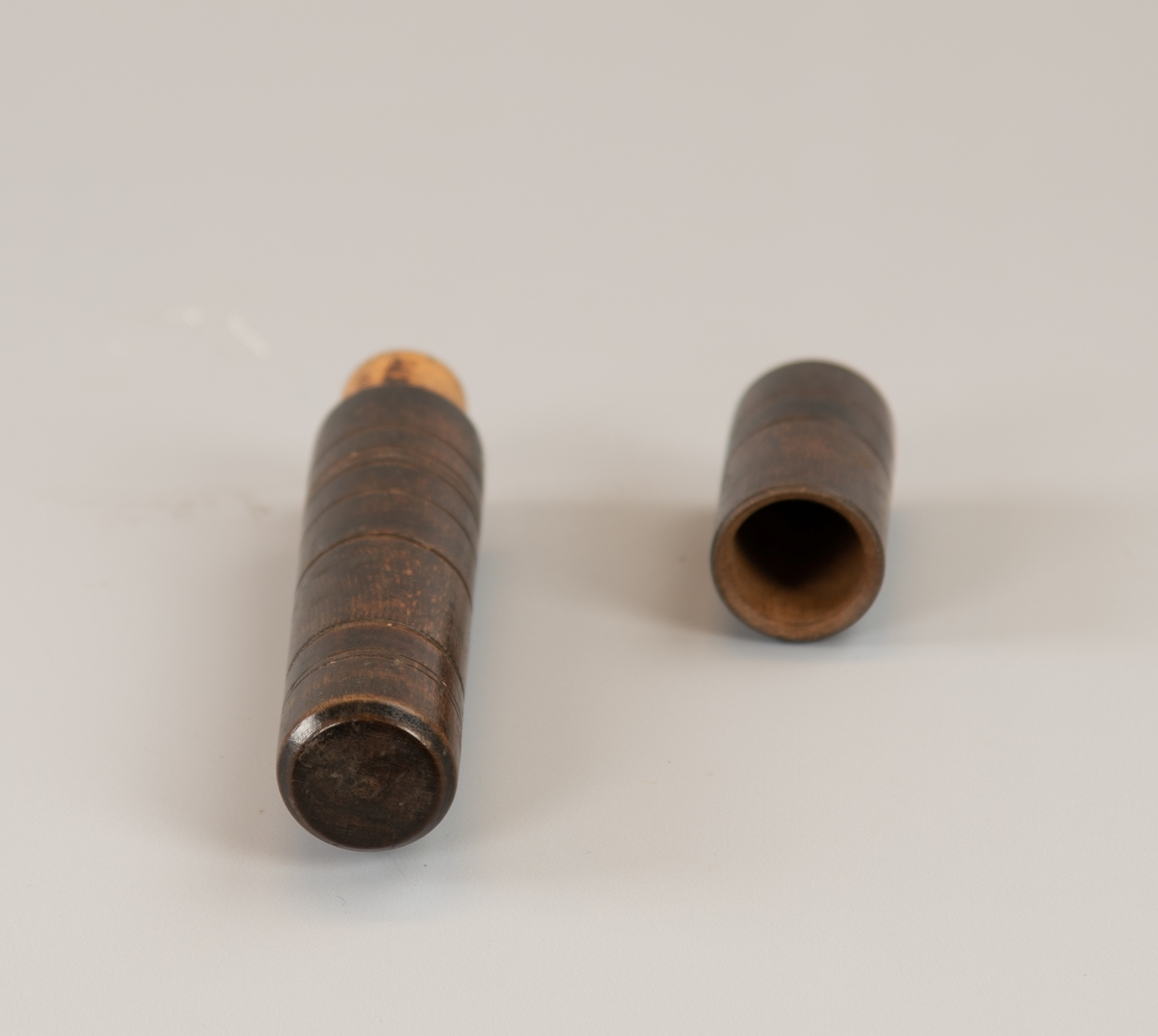 Smal sylinder med innskårne ringer. Lokk.