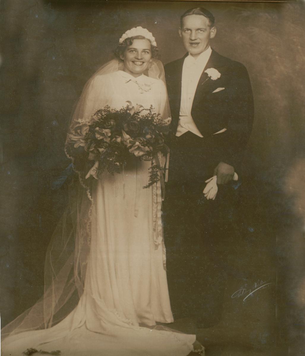 Smal kjole med langt slep. 3 bredde og innsatte kiler i skjørtet. Forbredden går opp i en spiss helt til halsåpningen, sidestykker lett rynket til denne og danner lett blusende fasong- Bak er skjørtet fastsydd til ryggen i livlinjen Lange puffermer.  Knappes bak med 19 kuleknappe og hemper av stoffet.  Brukt som brudekjole først av Ella Viktoria Hjallum i 1939. Hun giftet seg i Fagerborg kirke. Brukt 2. gang av datter Venke Hjallum Hagen ca. 1965 i Drammen