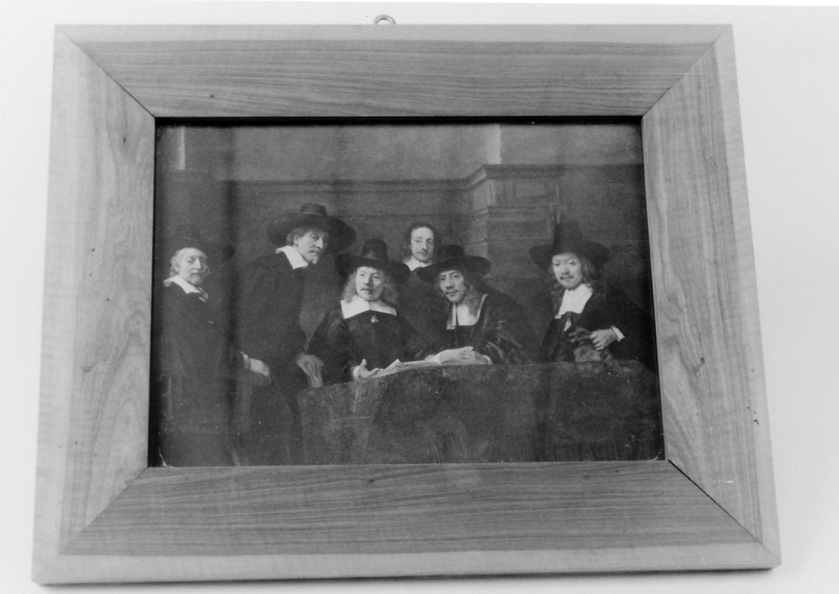 """Rektangulær ramme i bjerkefiner. Gruppeportrett, 5 herrer m. hatter omkr. et bord i bakgr. tjener. Motiv: """"Staalmeesters"""" (f.1661)"""