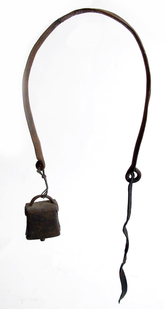 Kuklave av jern, med  lærrem og bjellle. U-formet klave av jernbånd, innvendig  rundet,  og med endene avsmalnet og bøyd i ring,  som feste for lærrem, og i den andre :  bjelle. Bjellen har rektangulær åpning  med sylindrisk kolv, rette, avsmalnende  sider og rund hankering tvers over.  Tilstand: rusten.