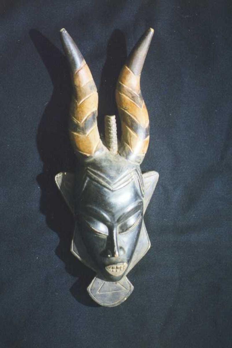 Sortfarget menneskeansikt med tre horn.