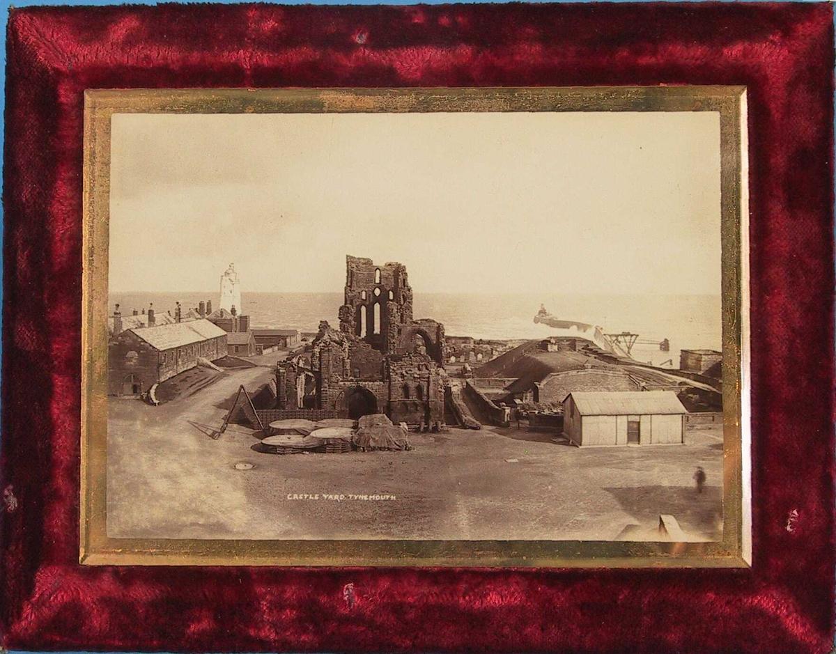 Prospekt fra Tynemouth, England.  Castle Yard, Tynemouth.   Slottsruiner  omgitt av   pakkboder, fyrtårn og molo.