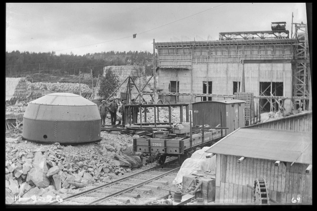 Arendal Fossekompani i begynnelsen av 1900-tallet CD merket 0468, Bilde: 70 Sted: Flaten Beskrivelse: Maskindeler og vogner foran kraftstasjonen