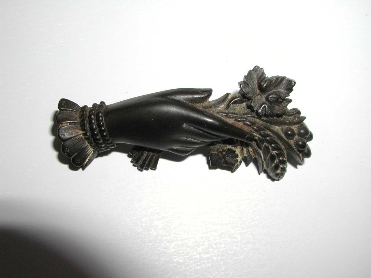 """Smykker   Smykkene er muligens i materialet """"jet"""" eller i et materiale som etterligner jet (en eller annen type stein eller muligens glass). Jet-smykker ble tatt i bruk som sørgesmykker under Dronning Victoria, og fikk stor utbredelse. Det er uvisst om disse smykkene har vært brukt som sørgesmykke."""