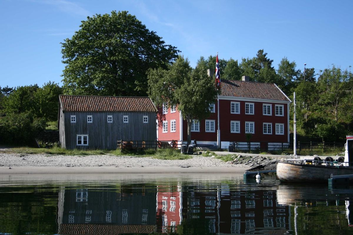 Merdøgaard, gårdstun sett fra N, sjøbod og våningshus. Tuntreet, en stor lønn, synlig over sjøboden.
