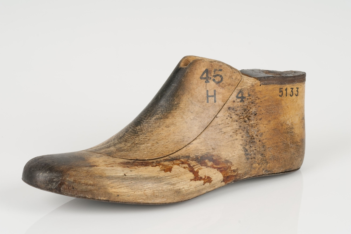 En tremodell i to deler; lest og opplest/overlest (kile) Venstrefot i skostørrelse 45. Hælstykket av metall. Lestekam av skinn.