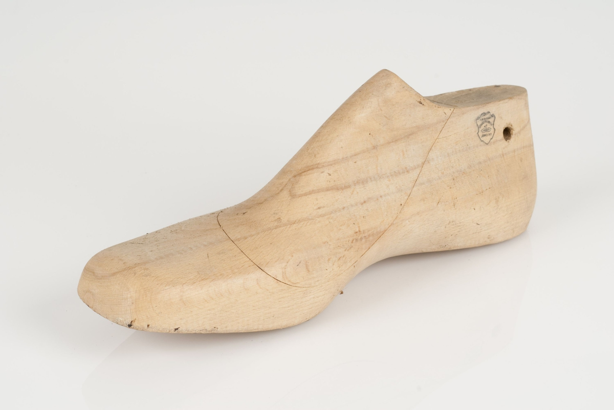 En tremodell i to deler; lest og opplest/overlest (kile) med påført tekst. Høyrefot i skostørrelse 45, og 9 cm i vidde.