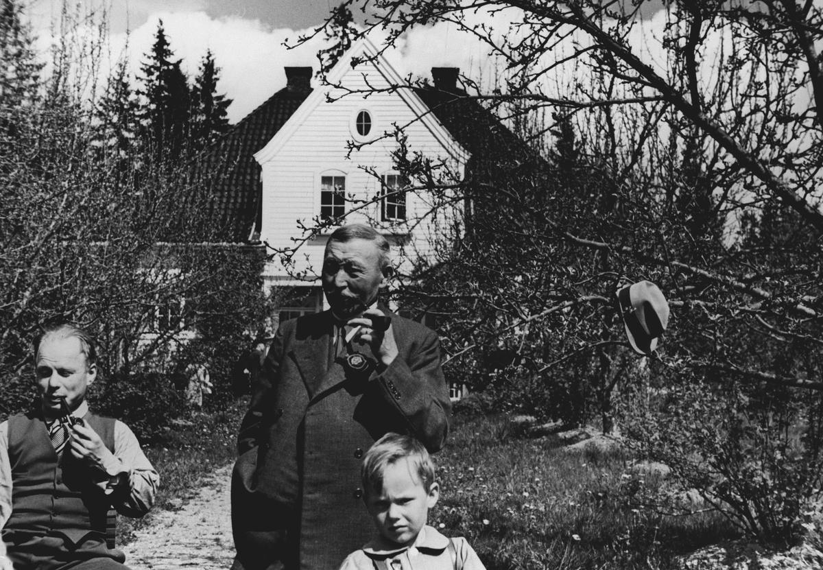 2. menn, 1. barn utenfor huset fra jubileumsutstillingen i 1914