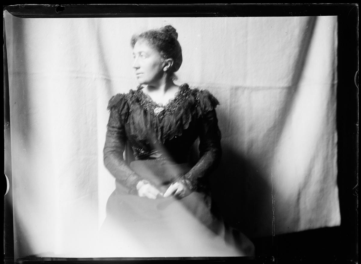 Mathilde Mathiesen i sorte klær foran et forheng.