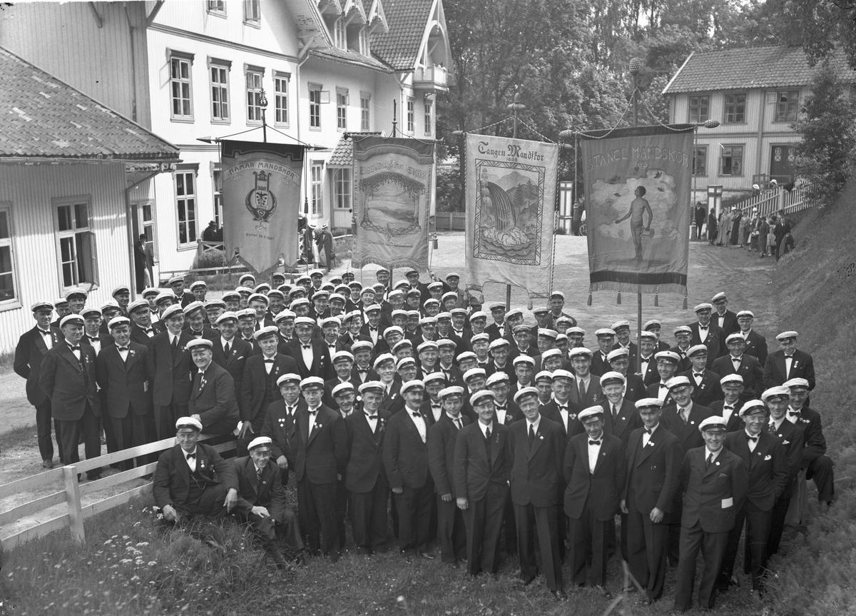 """Sangkor utenfor Eidsvoll Bad. Faner med: Hamar Mandskor – """"Stiftet 1907"""", Eidsvoll Mannskor – """"Sangen er vår lysning"""", Tangen Mandskor 1888, Stange Mandskor 1905."""