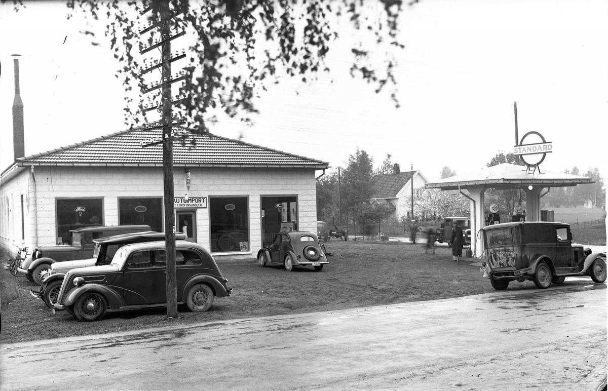 Autoimport. 5 biler foran forretningen.