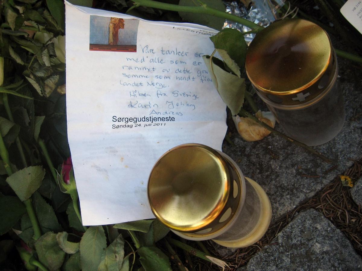 Minner etter terrorhandlingen den 22. juli 2011. Kort og lykter ved Krigsmonument ved Lillestrøm kirke.