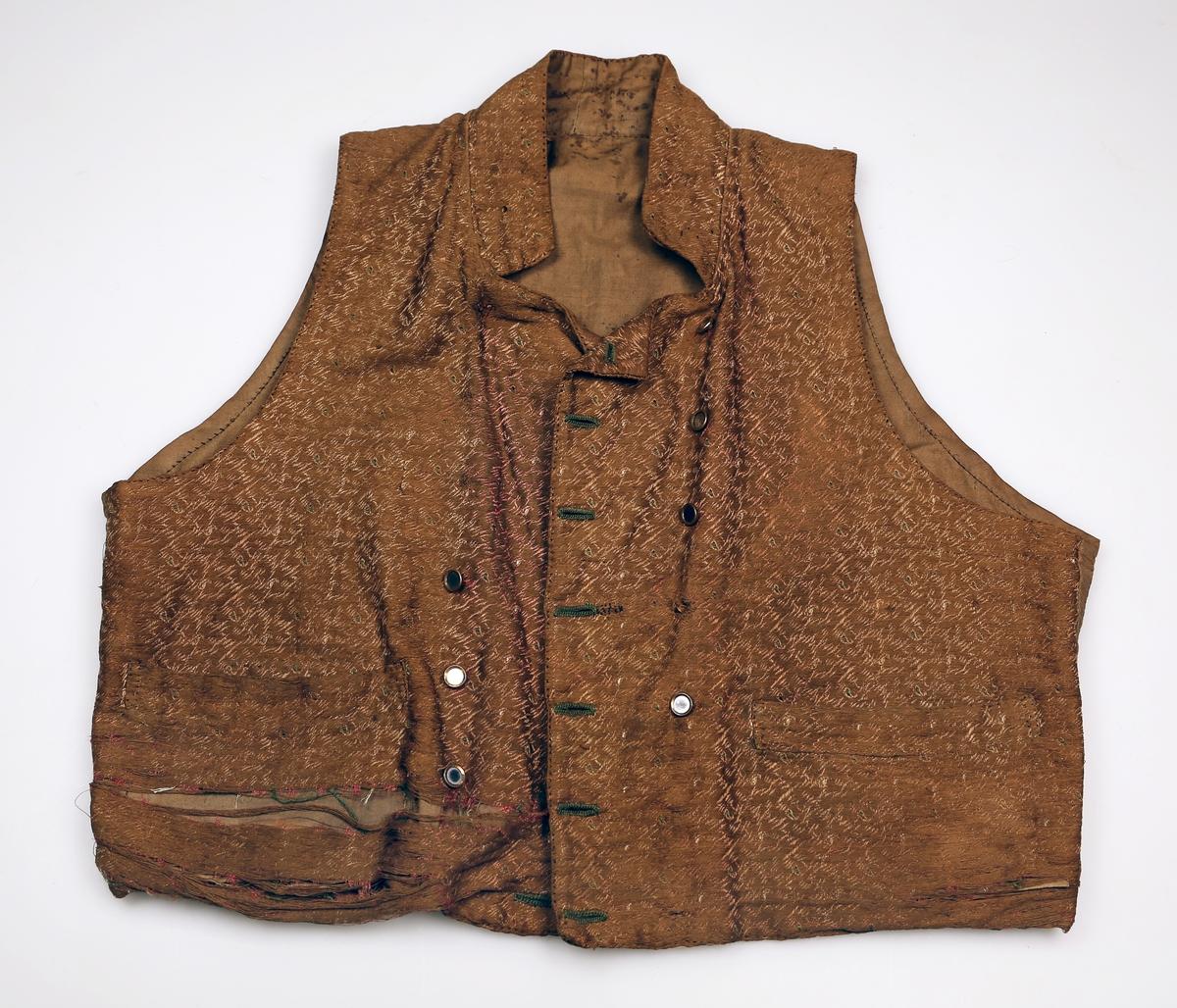 Vest med silkestoff og speilknapper i dobbelknepping, stående krage, og rygg samt fôr til forstykket i bomull. Vesten har to lommer foran.