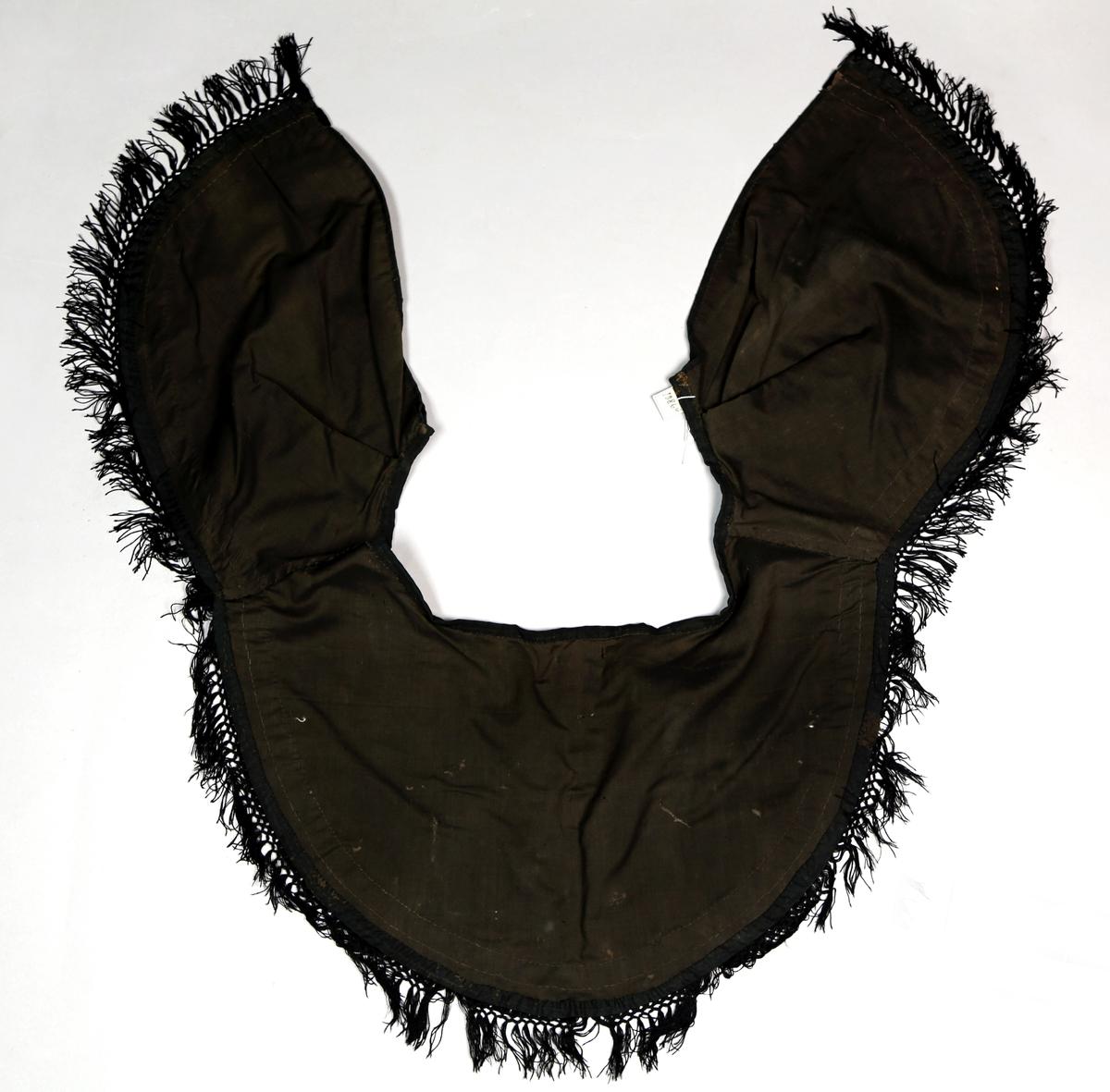 Krage som henger over skuldrene og er rund i formen. Den har fløyelsbånd og i nedkant bånd med frynser. Festes med hekter.