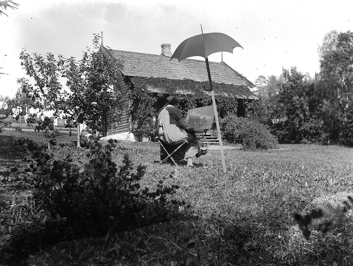 Kvinne under parasoll sitter og maler i hage. Aagot Olssøn, Kvalstua, Helgøya.