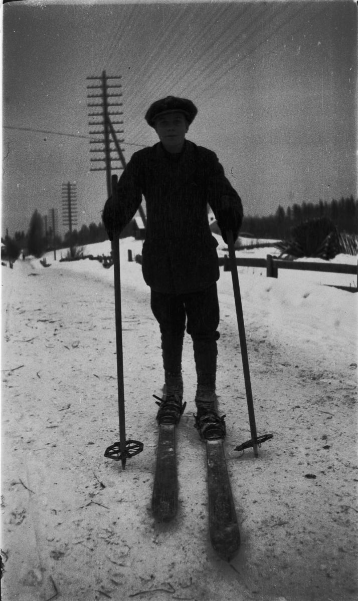 Ukjent person går på ski langs en vei.
