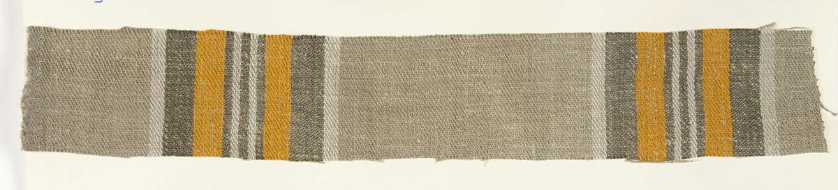 """Vävprov ämnat för bolstervarstyg, kypert. Randigt i grått och orange. Vävprovet är uppklistrat på en kartong i storleken 22 x 28 cm. I övre högra hörnet finns en stämpel """"Uppsala läns hemslöjdsförening"""" och ett handskrivet nummer, """"A.1591""""."""