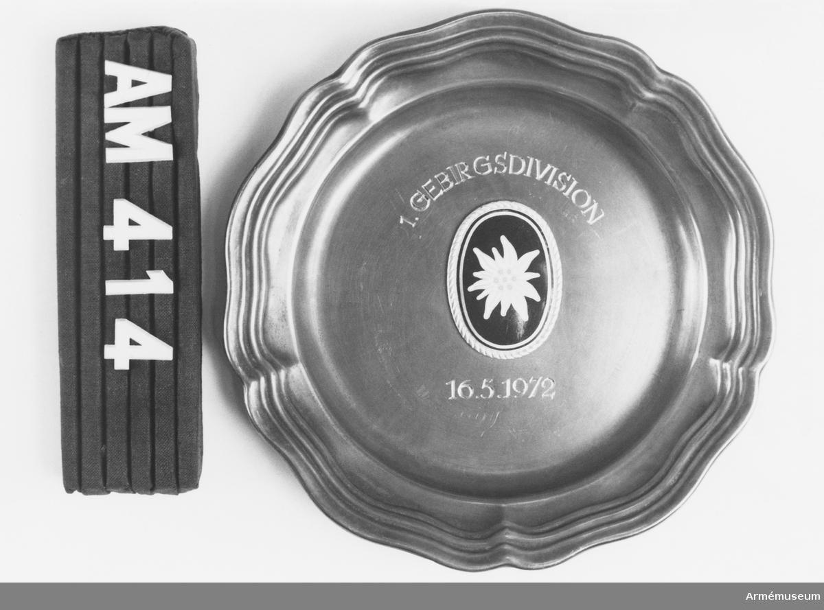 """Samhörande nr är 294-299, 321-350, 400-448. Tallrik med Edelweissmotiv. Från 1. Gebirgsdivision, mottagen 1972-05-16 av CA under besök vid Västtyska armén i maj 1972. I tallrikens mitt en vit edelweiss med gula pistiller på mörkgrön botten. Omgiven av en snodd i silver. Däröver graverat i båge: 1.GEBIRGSDIVISION. Under blomman graverat, rakt: 16.5.1972 På tallrikens undersida finns ett """"änglamärke""""++AS."""