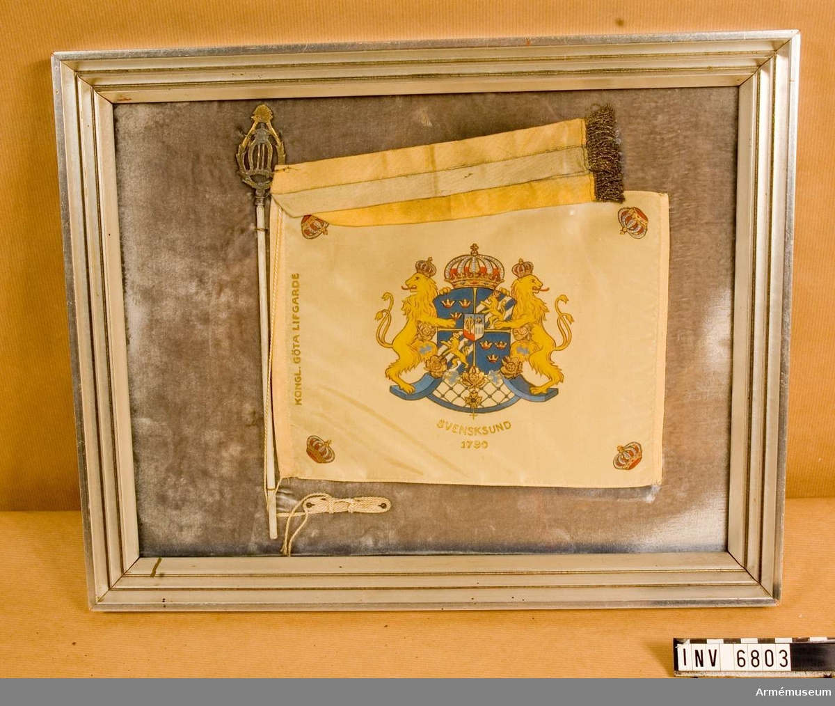 """Format på tavlan: 440 x 355 mm, standar: 240 x 185 mm. Bordsstandar av gulvitt ripssiden med riksvapnet kronorna och segernamnen målade i färg och guld och silver. Kopierad efter Göta livgardes fana m/1894. Fäst mot vitmålad metallstång och med förgylld spets med Oscar II:s monogram. Tavlan har silvermålad träram och under glaset ligger standaret på en botten klädd med grå sammet. Med ligger också en blå och gul kravatt med guldfrans. Kravatten är mycket blekt.   På tavlans  baksida står det skrivet: """"Gåva från Major Frans Albert Schartaus sterbhus till undertecknad 1943. Skall efter min död  Överlämnas till Kungl. Göta Livgardes minnesmuseum. Carl Hugo  Broms""""."""