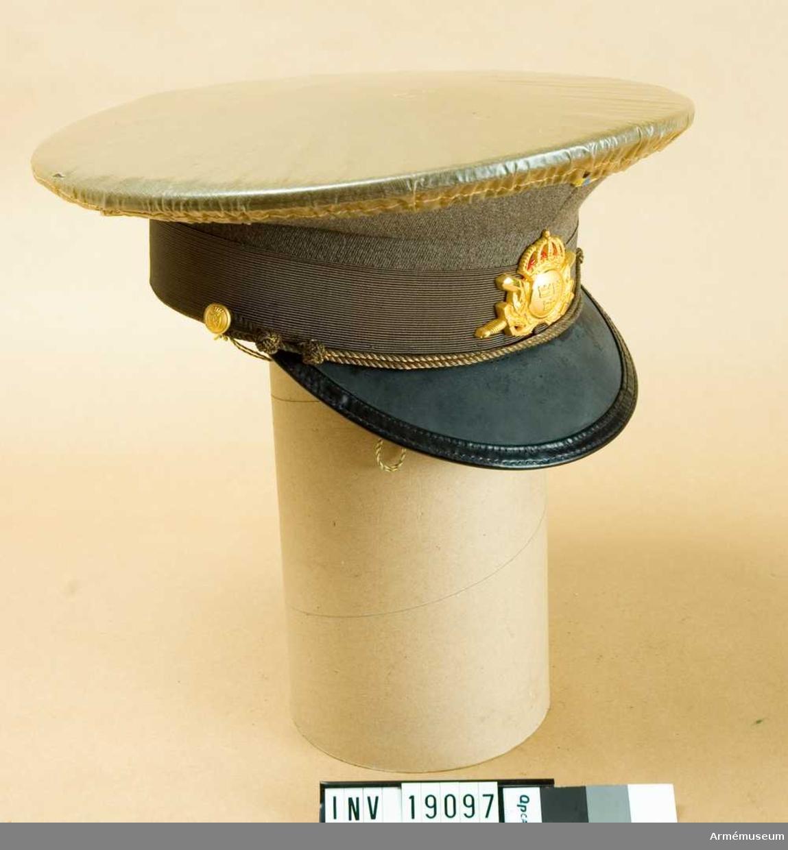 Av yllediagonal i gråbrungrön färg. Lackskärm, svart med grön undersida. Grått ripsband och tunn snodd av bronsfärgad metall som knäppa fast vid mössan på två små knappar, mattförgyllda för Skaraborgs reg. Mattförgyllt mössmärke m/1952 och nationalitetsmärke m/1941. Strimmel 50 mm. Kullens bredd: 28-30 mm; bredden kanten bak: 45 mm. Mössöverdrag av genomskinlig plast med resårband kanten. Mössans styvnad får ej borttagas och mössöverdraget får bäras endast då väderleken gör det nödvändigt.