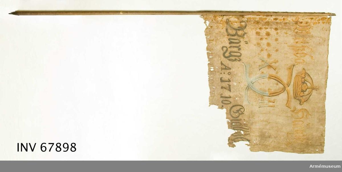 Duk: Tillverkad av enkel vit linnelärft, sydd av två horisontella våder. Duken fäst vid stången med järnskenor.  Dekor:  Målad endast på dukens insida, i mitten Karl XII:s namnchiffer, dubbelt C med X-II på ömse sidor, krönt med sluten krona, i gult och brunt på det övre fältet, i blått och svart på det nedre. Text på ömse sidor om chiffret; upptill gul med konturer i brunt och nedtill i svart.  Stång: Tillverkad i trä. Har en liten doppsko.