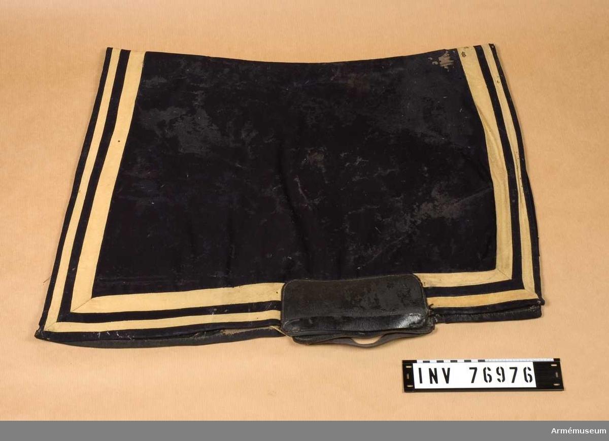 Grupp: K I.   Valltrappen eller sadeltäcket är försett med en bred och en smal list av guld kläde över mörkblått kläde.