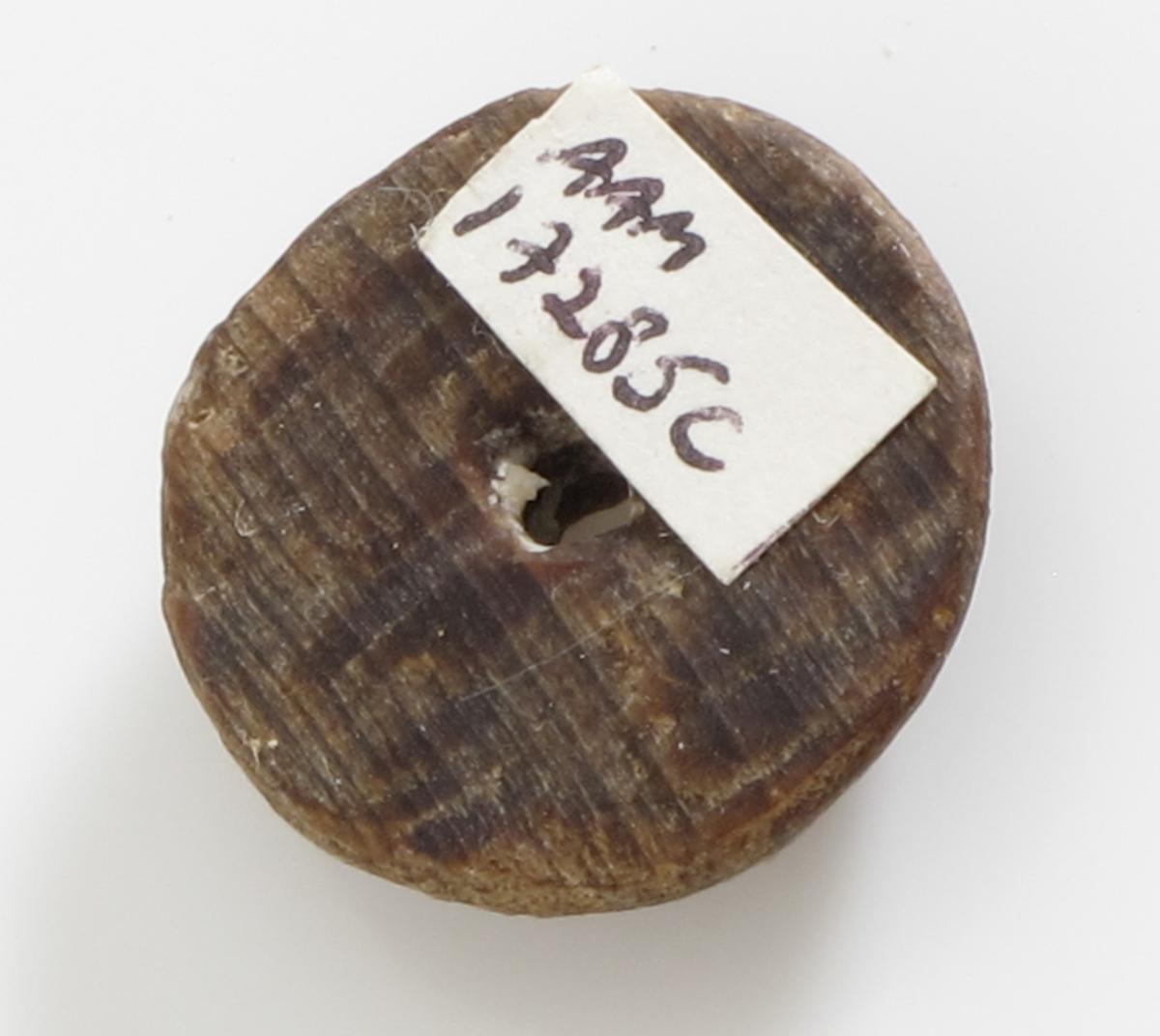"""Knapper, 11 stk.  """"Fredensborg,""""1768.   a)  Lærknapp. Diam. 2,1 Flat underside, overside med radiære riller, to hull. Et lite stk. borte i  kanten.    b-f )  Knapper, 5 stk., Tre,  med hvelvet overside og ett forholdsvis stort hull. Diam. 1,9.  y    g-i.)  Knapper, 3 stk. Tre. Tynne, små, med ett hull.   Diam. 1,2.  j-k )  Knapper, 2 stk. svakt hvelvet overflate,ett  hull, den ene avslått et segment. Diam. 2,1."""