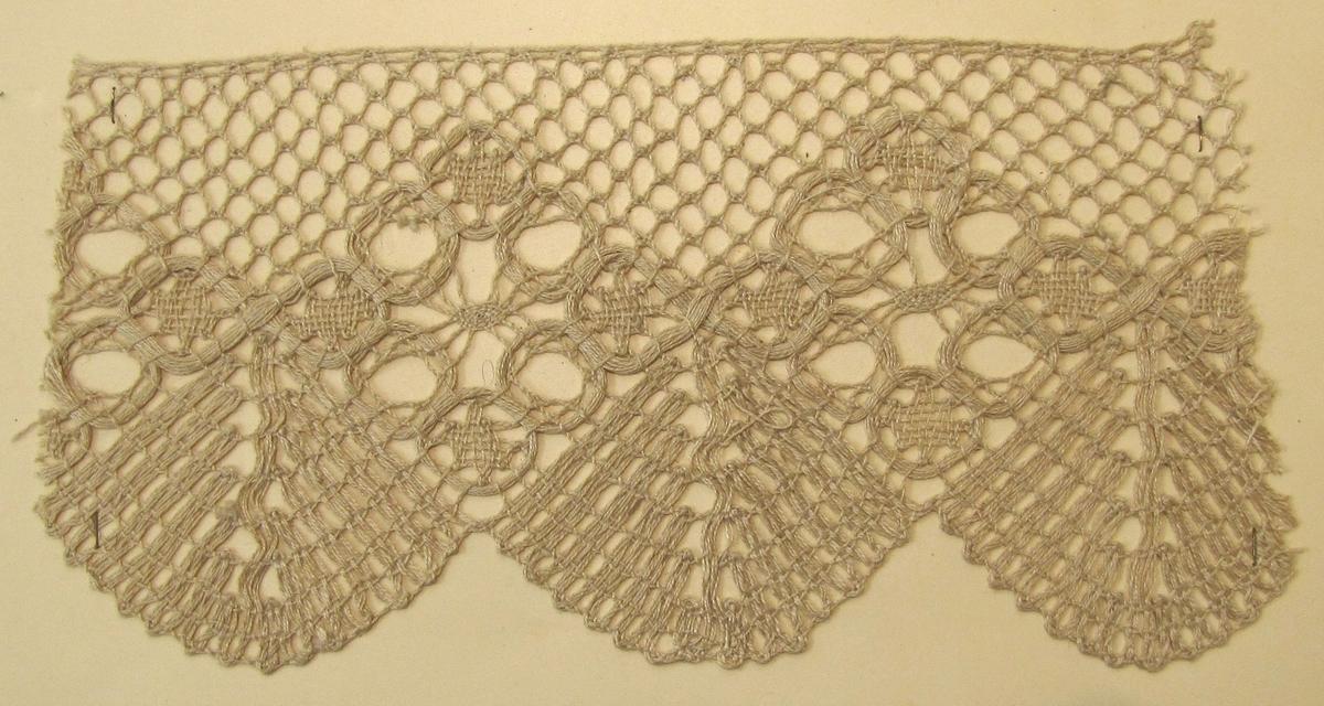 Spetsen är knypplad och har en nålhålsbotten. Mönstret består av spindlar med runda inramningar av mångdubbelt linne. De bildar tillsammans romboider, 14 av dem är vävbottnar. Uddarna är arbetade i vävslag? och delade på mitten, här har dubbelt garn använts.(oblekt ullgarn)    Denna spets ingår i samlingen svenska spetsar.