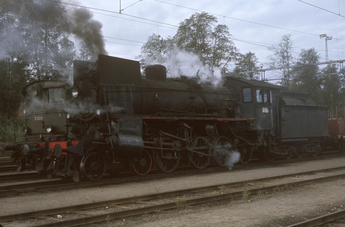 Elektrisk lok El 5 2035 og damplok 26c 434 med hvert sitt godstog på Kongsvinger stasjon.