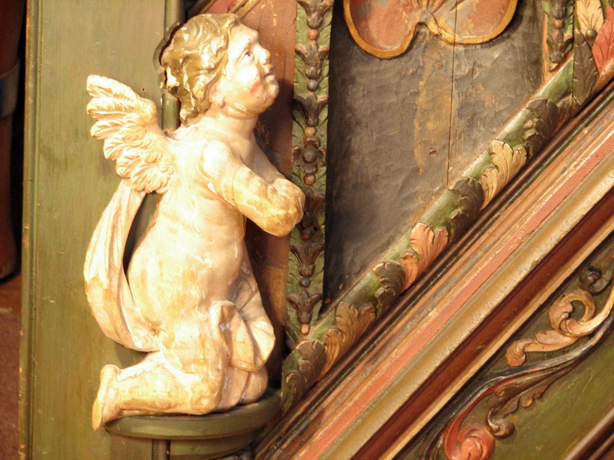 Knelende engel; utspilt forgylt vinge; hodet vendt oppover, begge armene frem over brystet. Begge armene avslått.